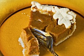 A piece of pumpkin pie with cake fork