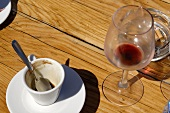 Empty espresso cup, red wine glass and an ashtray