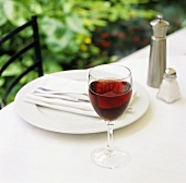 Place-setting with a glass of red wine out of doors