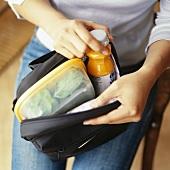 Frau packt Tasche mit Lunch Box und Smoothie