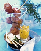 Bacon-wrapped cocktail sausages on cocktail sticks, mustard