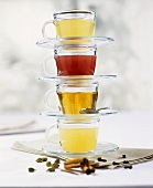 Four glass cups & saucers, each with a different tea, stacked