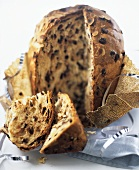 Almond and olive bread, partly sliced, on wrapping paper