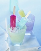 Coloured ice lollies in glasses of crushed ice
