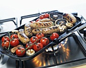 Sausages, mushrooms and tomatoes in a grill frying pan
