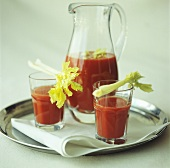 Tomato juice with celery in a jug and glasses