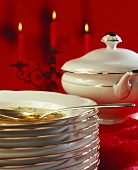 Stack of plates with soup in top plate, soup tureen