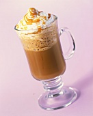 A glass of hot chocolate with whipped cream and caramel sauce