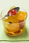 Candied fruit with mustard in glass with spoon
