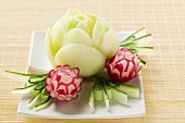 Large and small radish flowers with carved cucumber