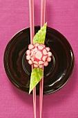 Radish flower on chopsticks, carved cucumber leaves