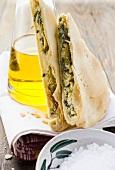Pieces of spinach & ricotta pie beside olive oil bottle, salt