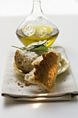 Pieces of white bread on plate with olive sprig, olive oil