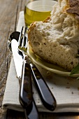 Pieces of white bread on plate, cutlery, olive oil