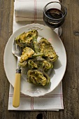 Stuffed artichokes with gratin topping, glass of red wine
