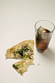 Slice of pizza with tuna, chard and olives, glass of cola