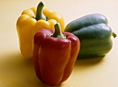 Red, yellow and green peppers with drops of water