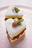 Heart-shaped cakes with jam, icing sugar, wild strawberries