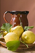 Fresh lemons with leaves on plate in front of terracotta jug