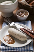 Cooked Weisswurst with mustard on plate
