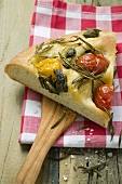 Slice of pizza with cherry tomatoes, capers and rosemary
