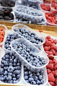 Blueberries and raspberries in plastic punnets at a market