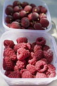 Fresh raspberries and gooseberries in plastic containers