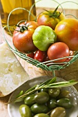 Assorted tomatoes in wire basket, olives, cheese