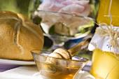 Honey in glass bowl beside bread roll