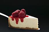 Slice of cheesecake with raspberries on cake server