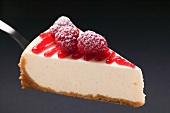Slice of cheesecake with sugared raspberries on cake server
