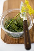 Dill in glass bowl with dill flowers on chopping board