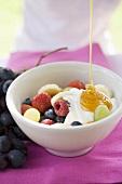Honig fliesst auf Fruchtmüsli mit Joghurt