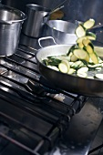 Tossing courgette slices in frying pan