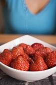 Erdbeeren in weisser Schale, Frau im Hintergrund