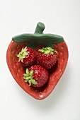 Three strawberries in red strawberry-shaped dish