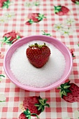 Strawberry in a small dish of sugar