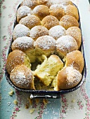 Buchteln (sweet yeast rolls) with icing sugar in baking tin