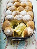 Buchteln (sweet yeast rolls) with icing sugar in baking tin