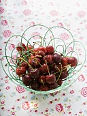 Cherries with drops of water in wire basket