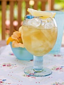 Fruity pineapple drink with ice cubes and lemon