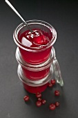 Three jars of redcurrant jelly, one opened, with spoon