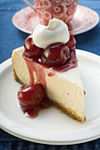 Piece of cheesecake with cherries and cream