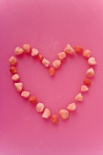 Small pink sweets arranged in a heart shape (outline)