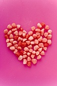 Small pink sweets arranged in a heart shape (solid)