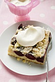 A piece of cherry crumble cake with cream