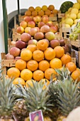 Fruit stall with oranges, pineapples and apples