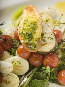 Sea bass cutlet with crostini on roasted vegetables