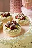 Meringue shells with raspberries, vanilla cream & icing sugar