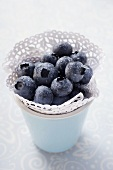 Fresh blueberries with drops of water in beaker
